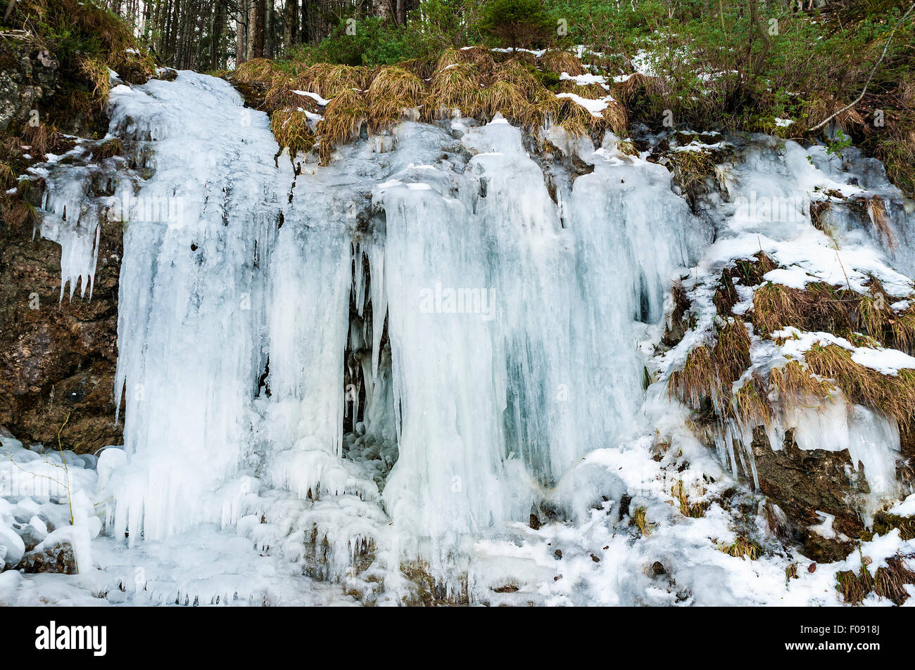 Frozen waterfall at lake Weissensee in Bavaria, Germany in winter - Stock Image