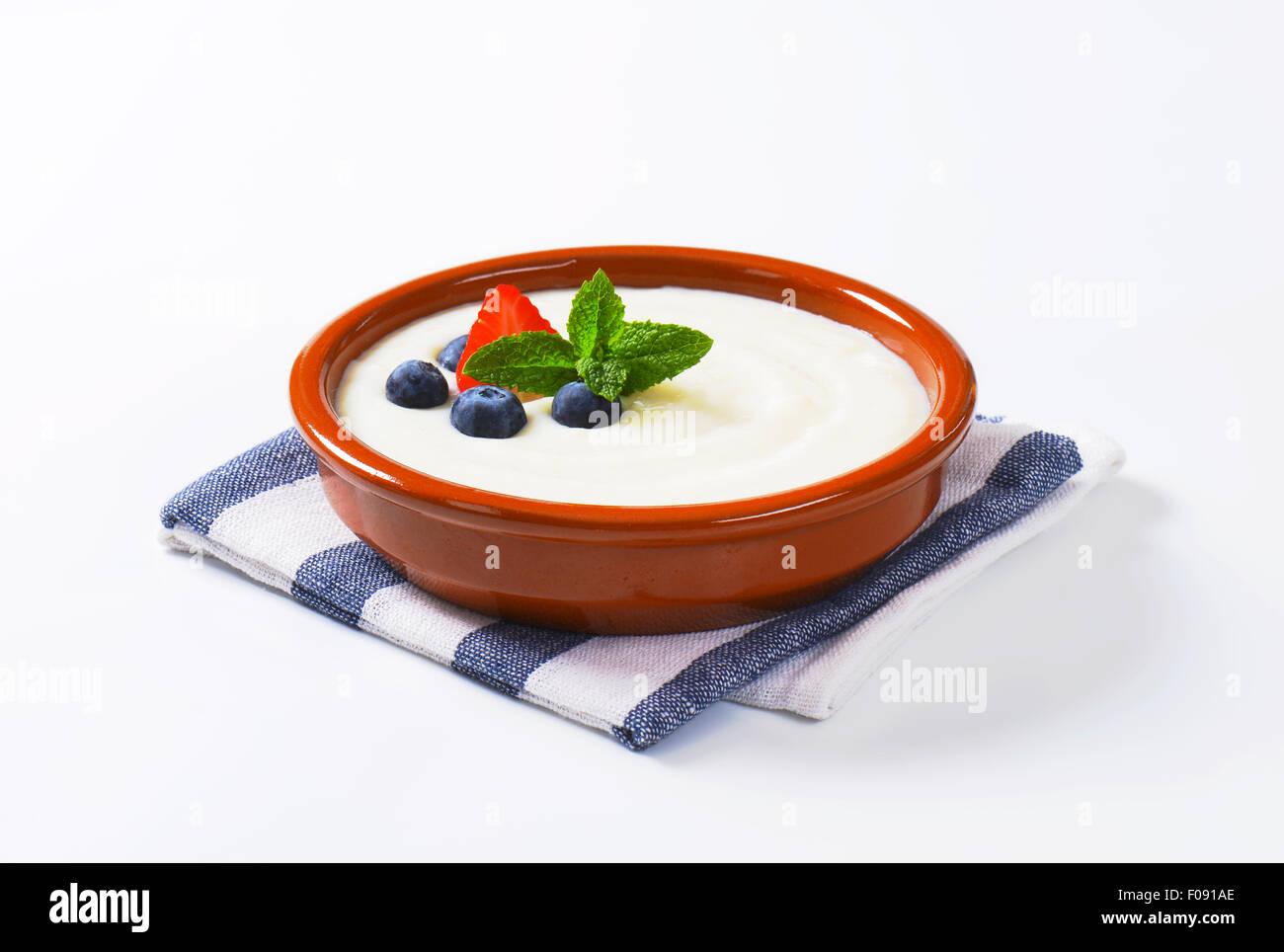 Smooth semolina porridge served in terracotta dish with fresh fruit - Stock Image