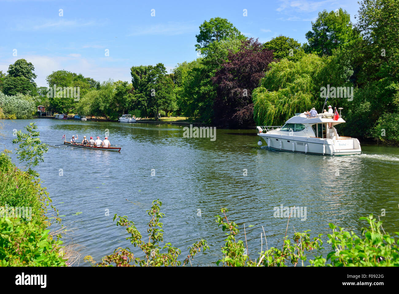 Jeanneau Prestige 32 Boat cruise boat and rowing boat on River Thames, Runnymede, Surrey, England, United Kingdom - Stock Image
