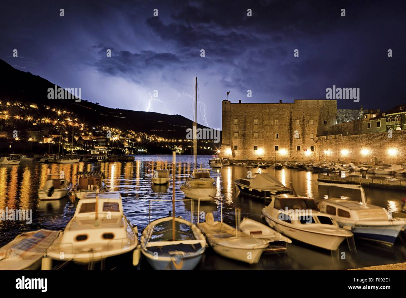 Boats moored on Dubrovnik old harbour with thunderstorm at night in Croatia Stock Photo
