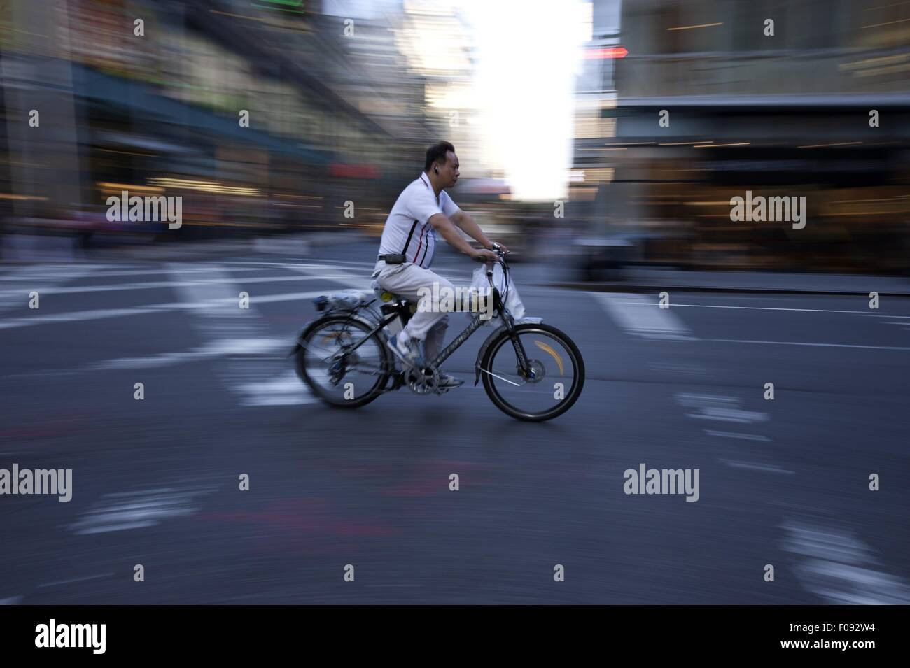Man riding bicycle on road, blurred motion - Stock Image