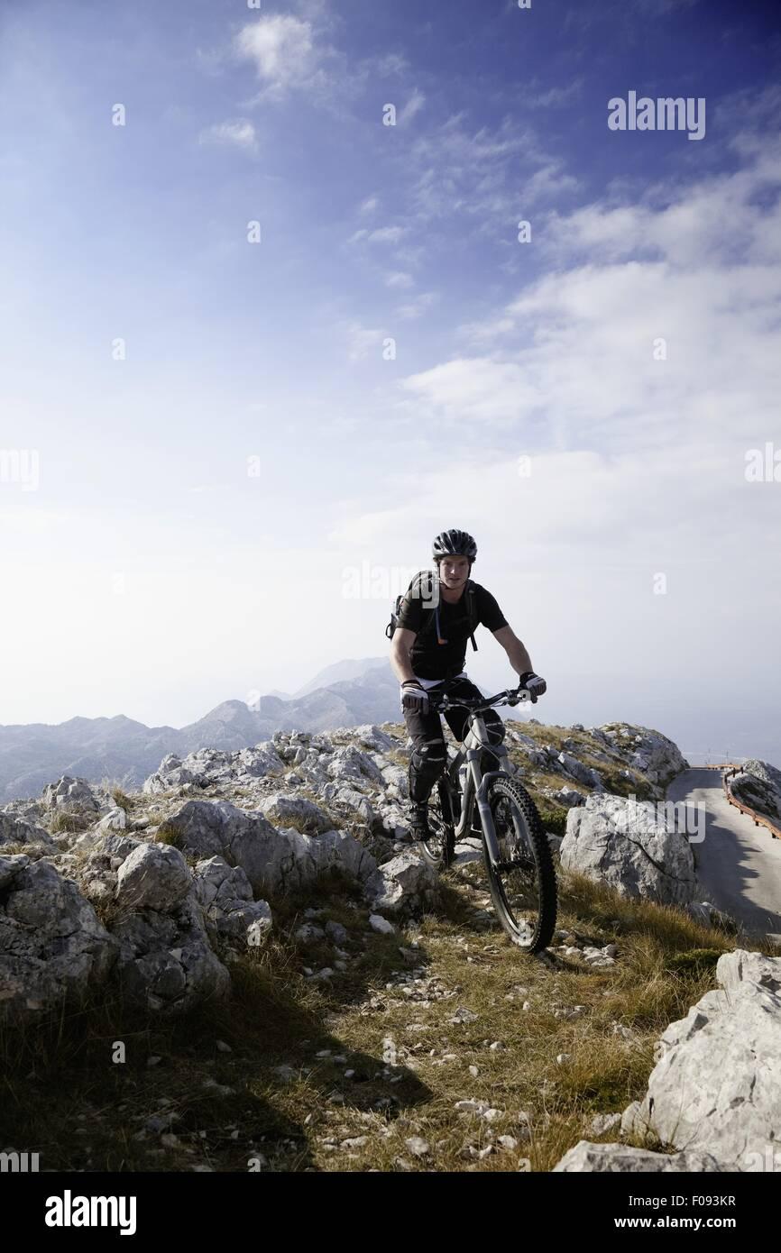 Biker riding bike on Mount Sveti Jure in Dalmatia, Croatia - Stock Image