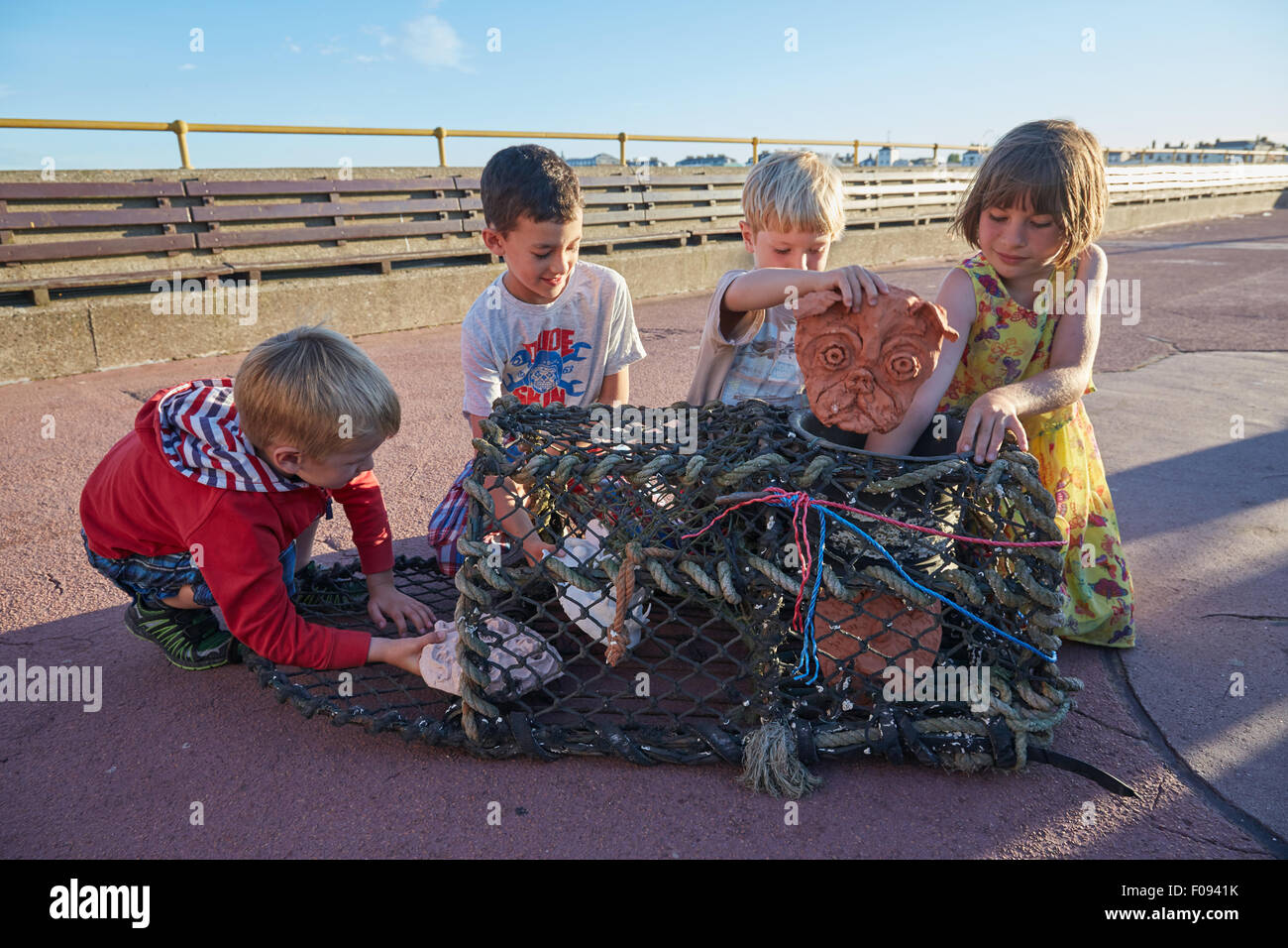 Deal, Kent, UK, Sunday 9th August 2015. Children put Cabbo masks into a lobster pot on Deal Pier, as part of the Stock Photo