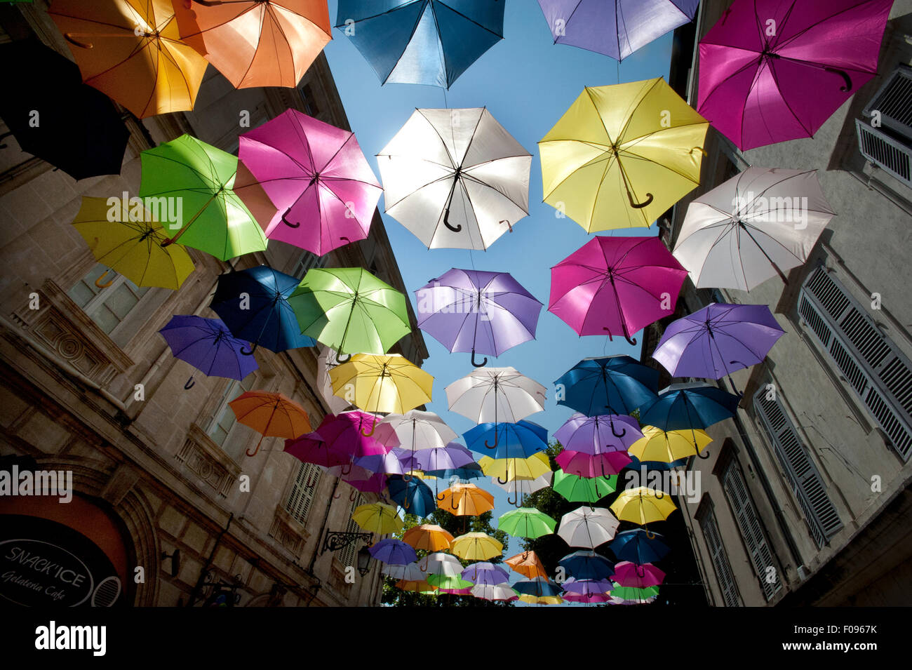 A sea of Brightly coloured floating umbrellas fill the sky above Rue Jean Jaures in Arles, Provence, South of France. - Stock Image