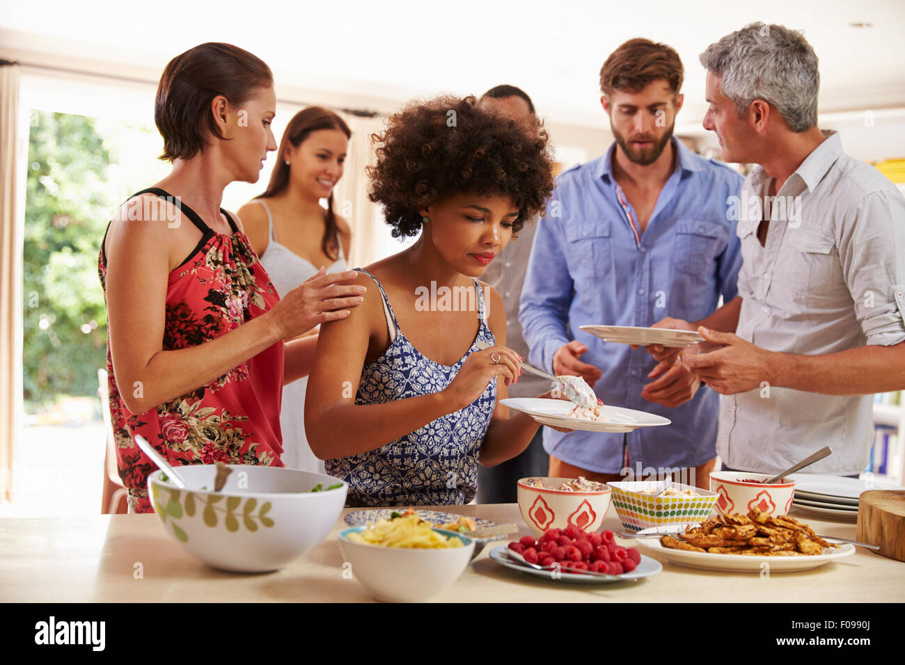 Friends serving themselves food and talking at dinner party - Stock Image