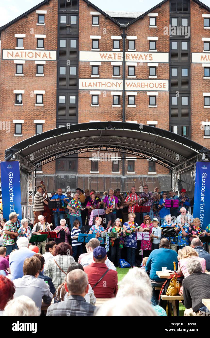 Friends Ukenited (mass ukulele band) performing at the Gloucester Tall Ships Festival 2015 in Gloucester Docks UK - Stock Image