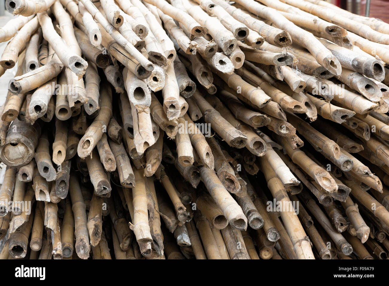 Bamboo scaffold poles stored ready to use on Hong Kong Island - Stock Image