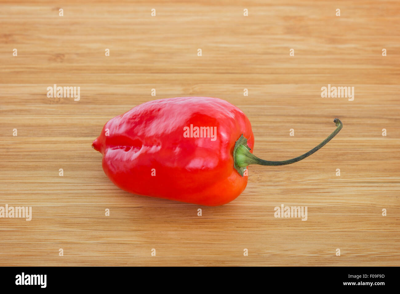 Close-up of a whole ripe red habanero chili on a wooden chopping board. Stock Photo