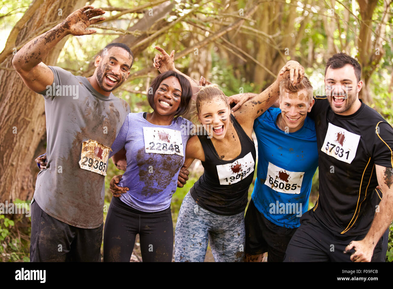 Competitors celebrate completing an endurance sports event - Stock Image