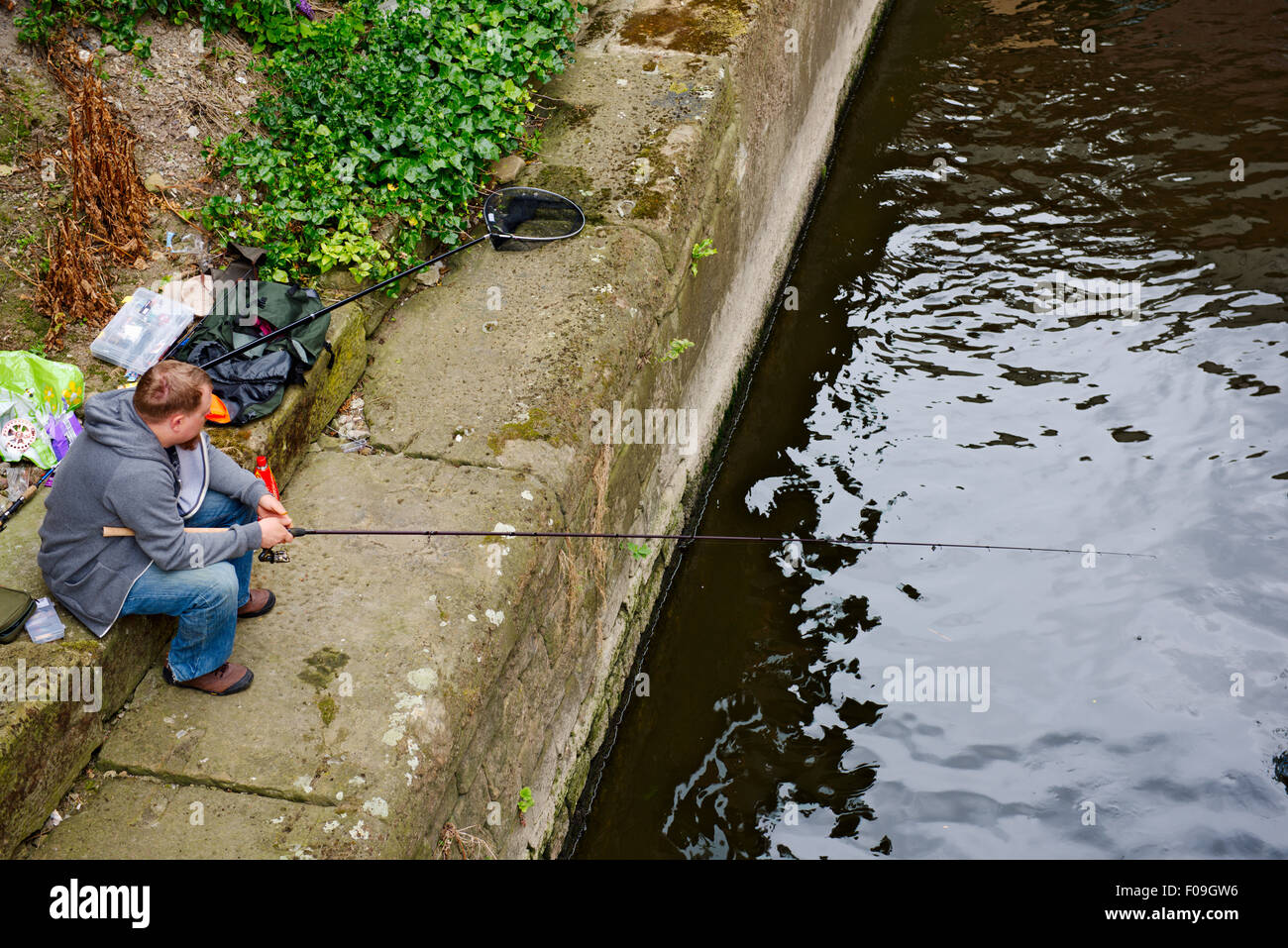 Man fishing in river Aire in central Leeds, West Yorkshire, UK - Stock Image