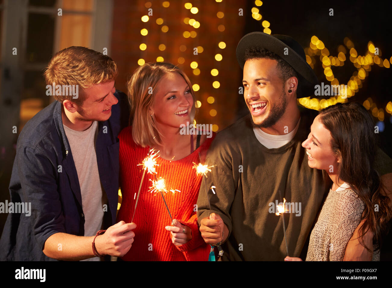 Group Of Friends Lighting Sparklers At Outdoor Party Stock Photo