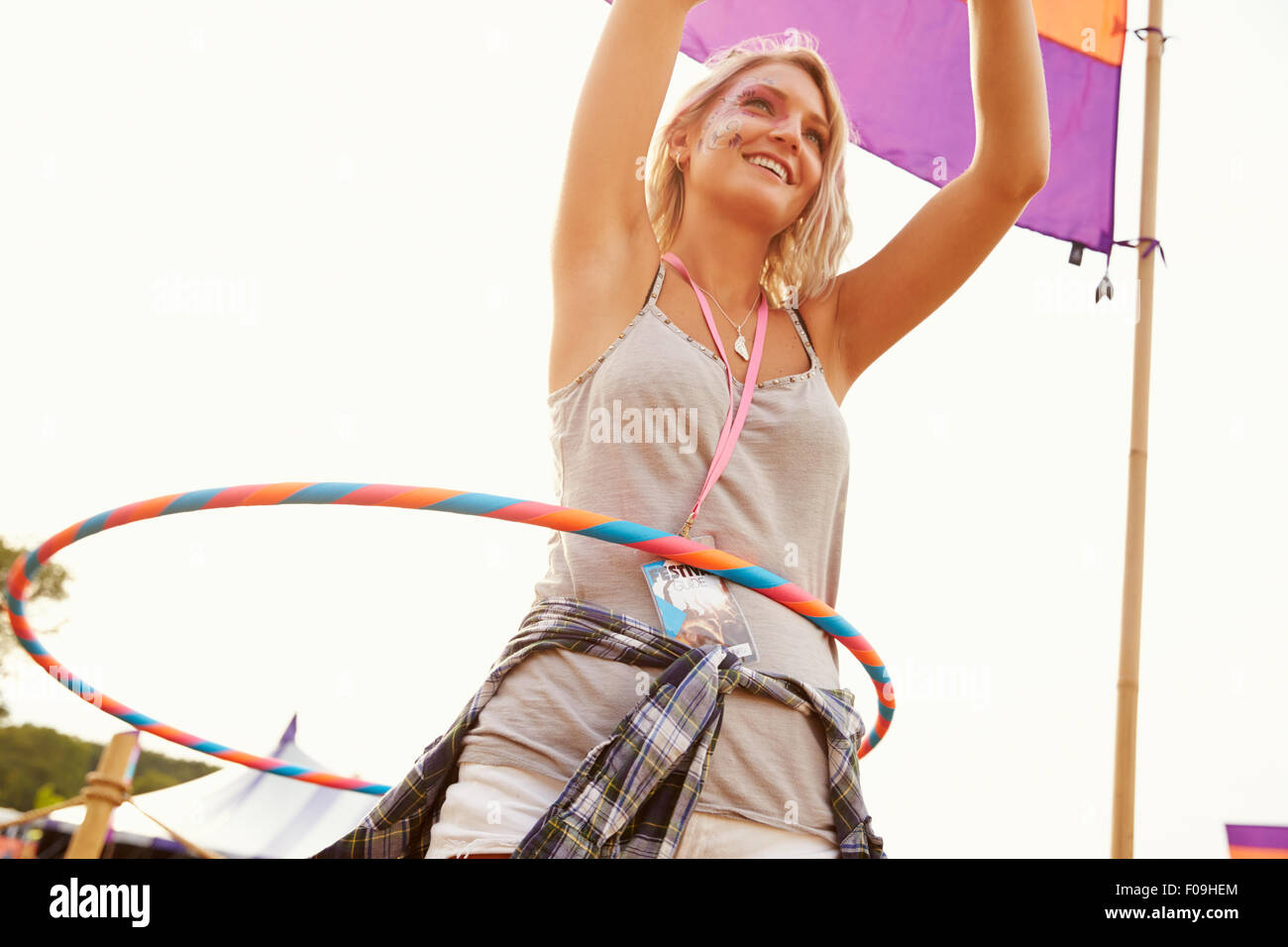 418f88de71 Blonde woman dancing with hula hoop at a music festival - Stock Image