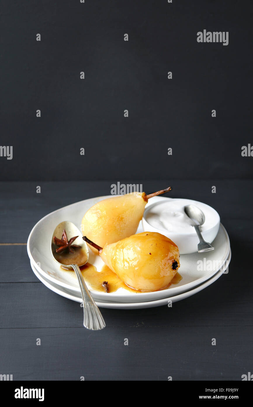Poached pears with caramel sauce and whipped cream - Stock Image