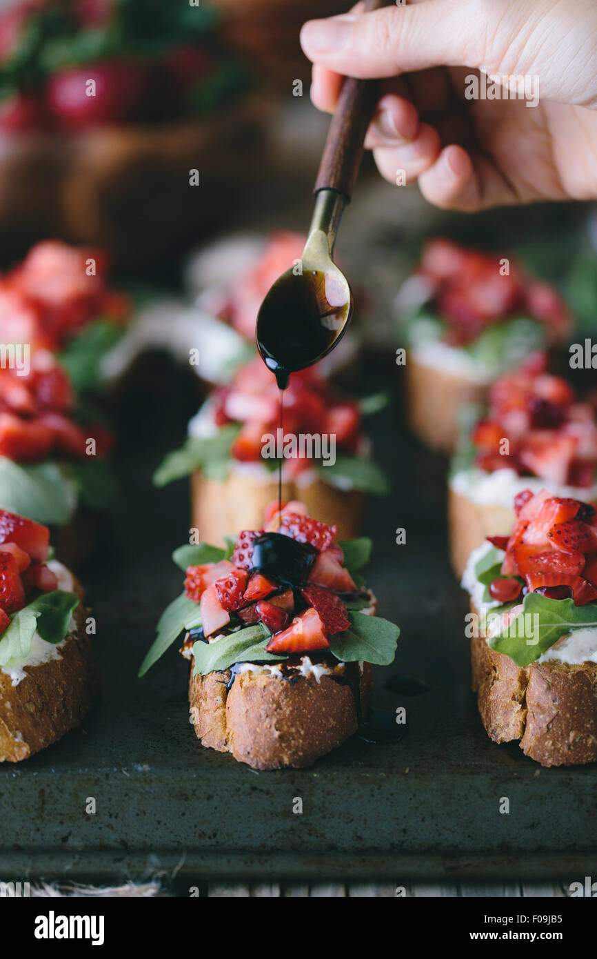 Balsamic reduction is being poured on a Strawberry and Ricotta Bruschetta by a woman. - Stock Image