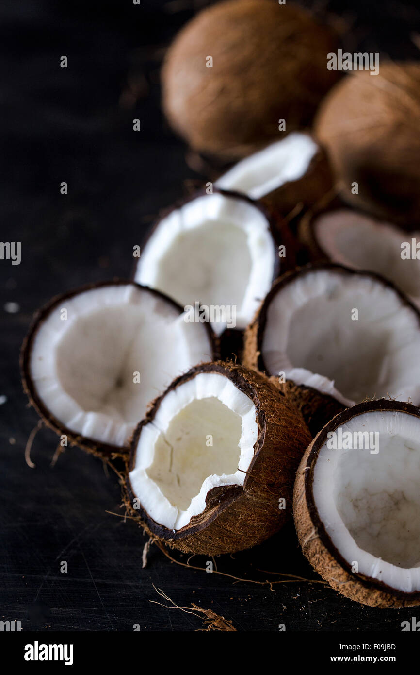 Fresh cracked coconuts are displayed on a dark background Stock Photo