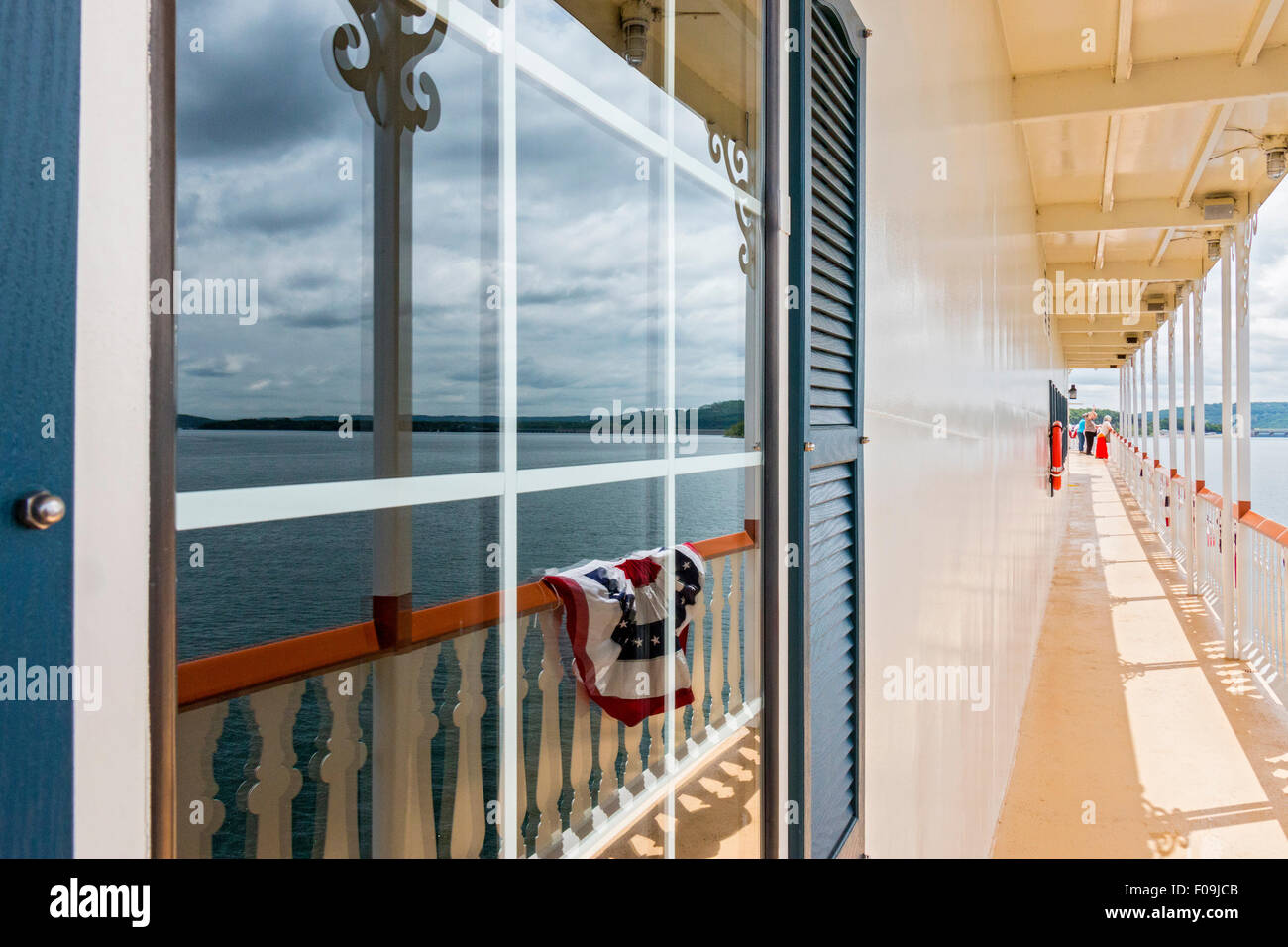 American flag drape reflected in the window along the outside deck walkway of the Showboat Branson Belle in Branson, - Stock Image