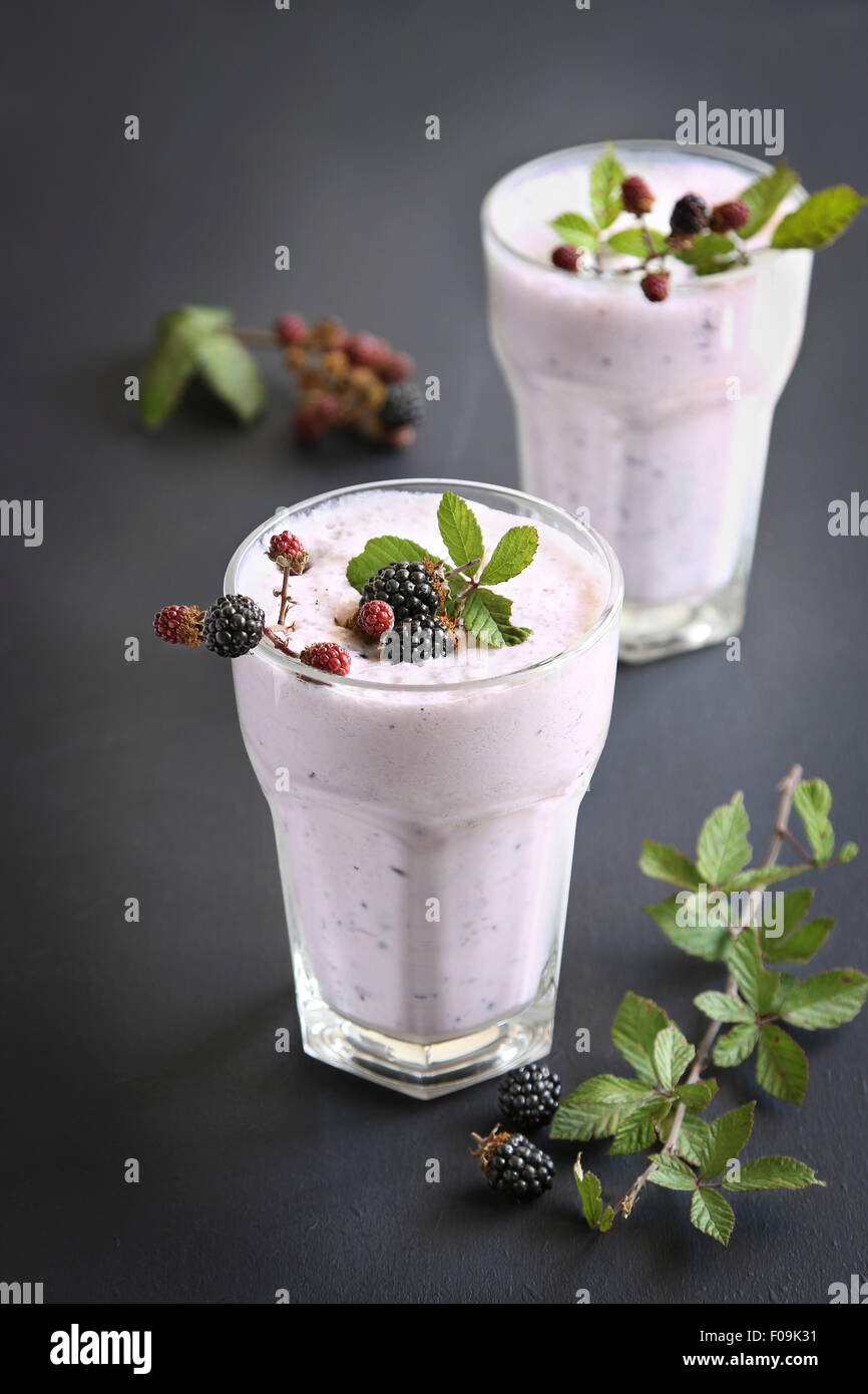 Two glasses with blackberry smoothie decorated with fresh blackberries - Stock Image