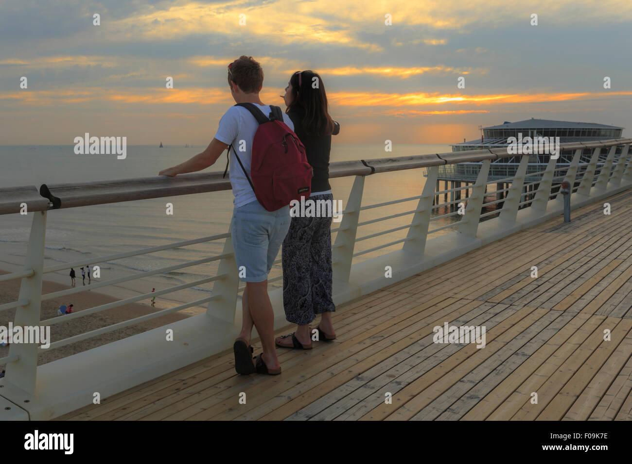Couple enjoying the sunset view from Scheveningen Pier on the upper deck, The Hague (Den Haag), South Holland, The Stock Photo