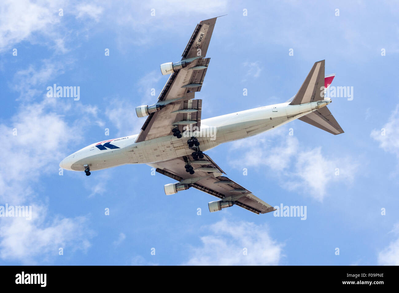 MK transport Boeing 747 flaying overhead with its wheels down while making approach to local airport. Blue and white Stock Photo