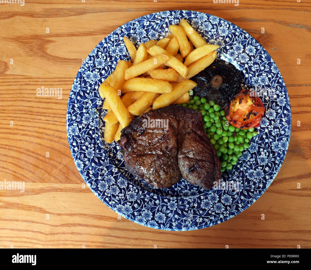 Steak & Chips meal on a blue and white plate. - Stock Image
