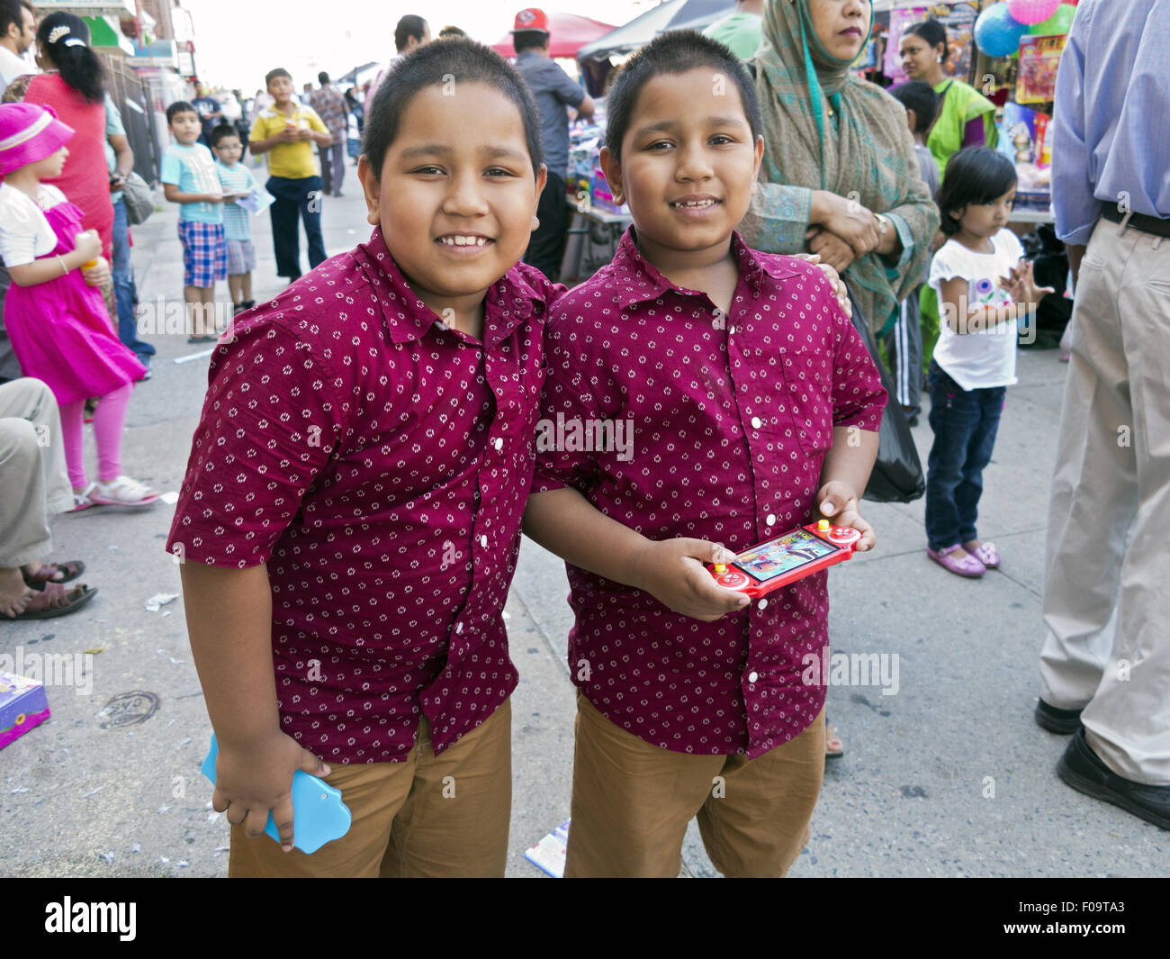 Eleven y.o. Identical twin boys at Bangladeshi street fair in 'Little Bangladesh' in the Kensington section - Stock Image