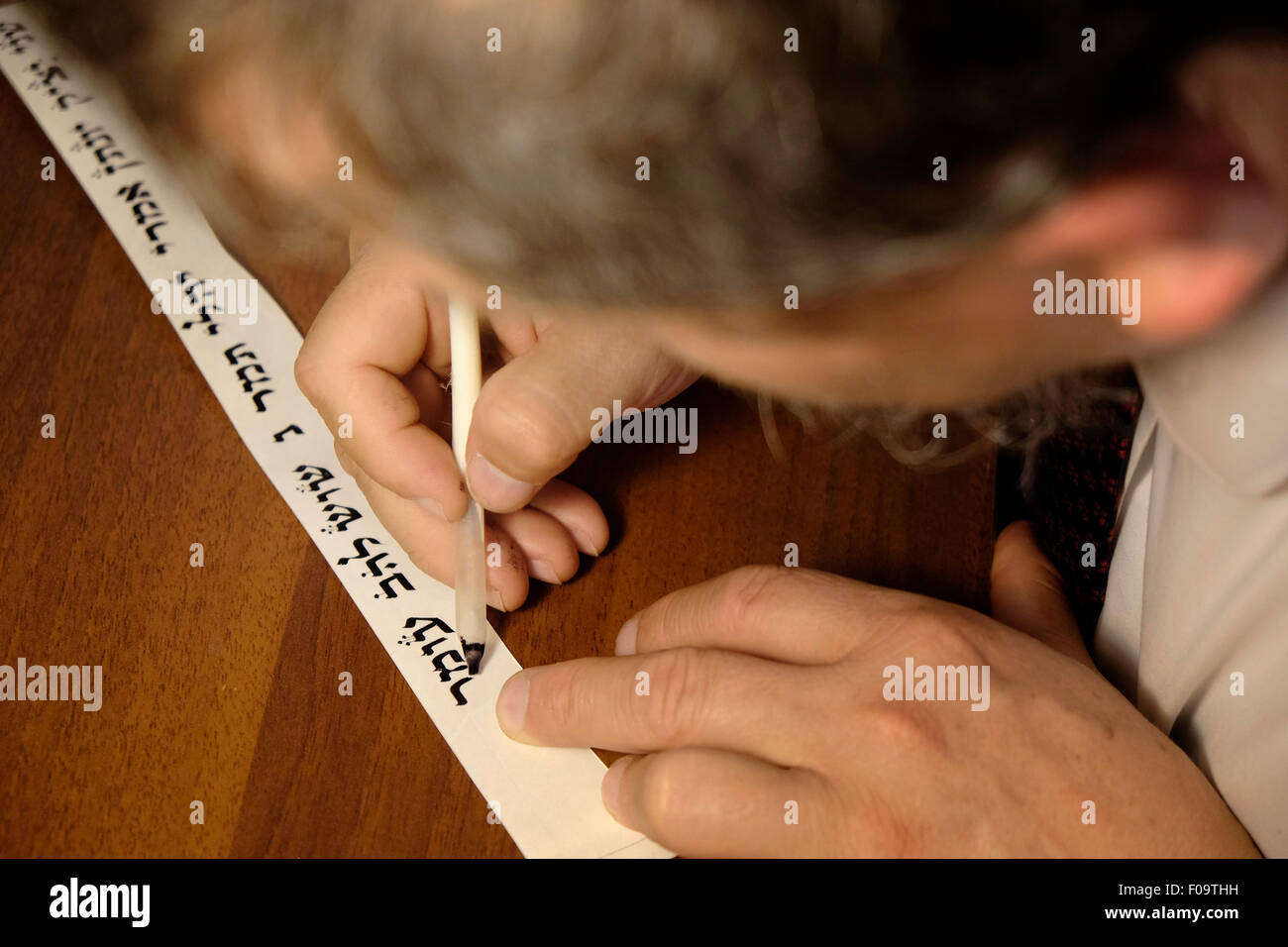 A religious Jewish 'Stam' calligrapher writing a Hebrew script on parchment in a Judaica workshop in the - Stock Image