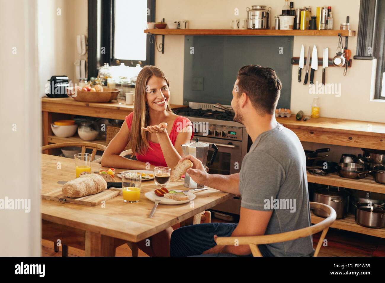 Happy young couple sitting at breakfast table in morning having a conversation. Young woman talking with her boyfriend - Stock Image