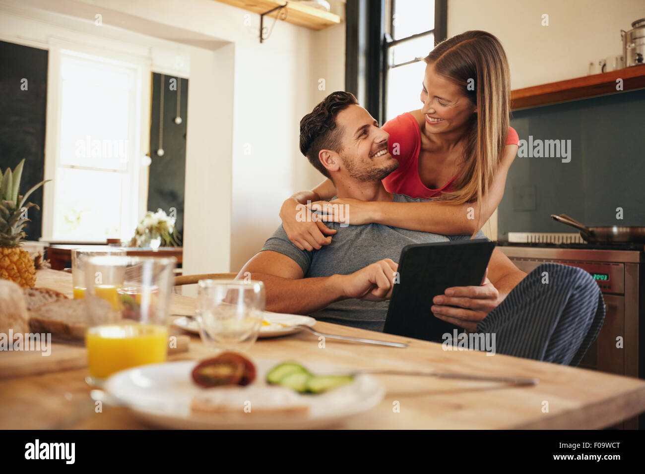 Shot of loving young couple in kitchen by breakfast table in morning. Man using digital table while woman hugging - Stock Image