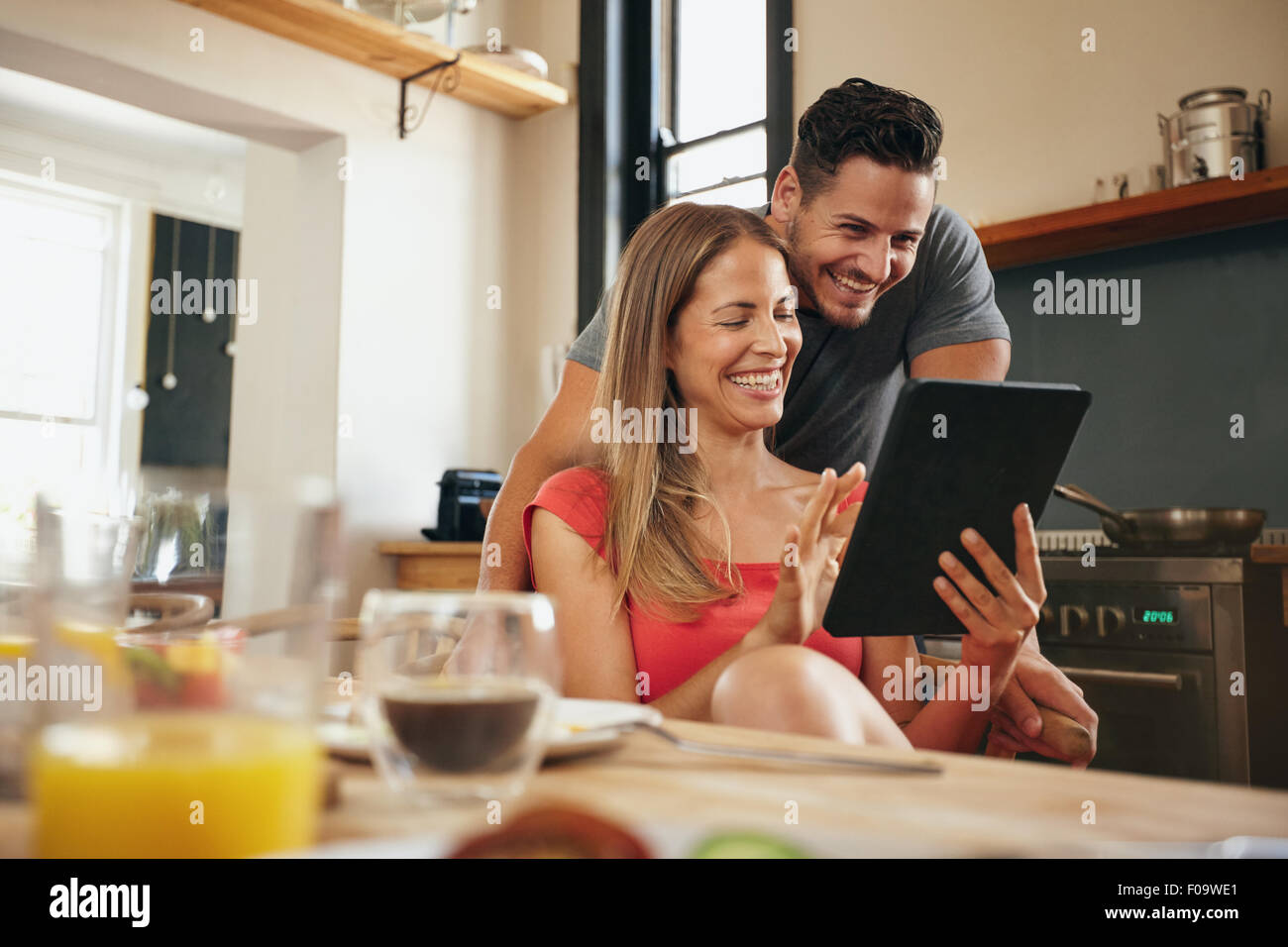 Happy young couple in the modern kitchen in the morning, using a digital tablet. Smiling young woman showing something - Stock Image
