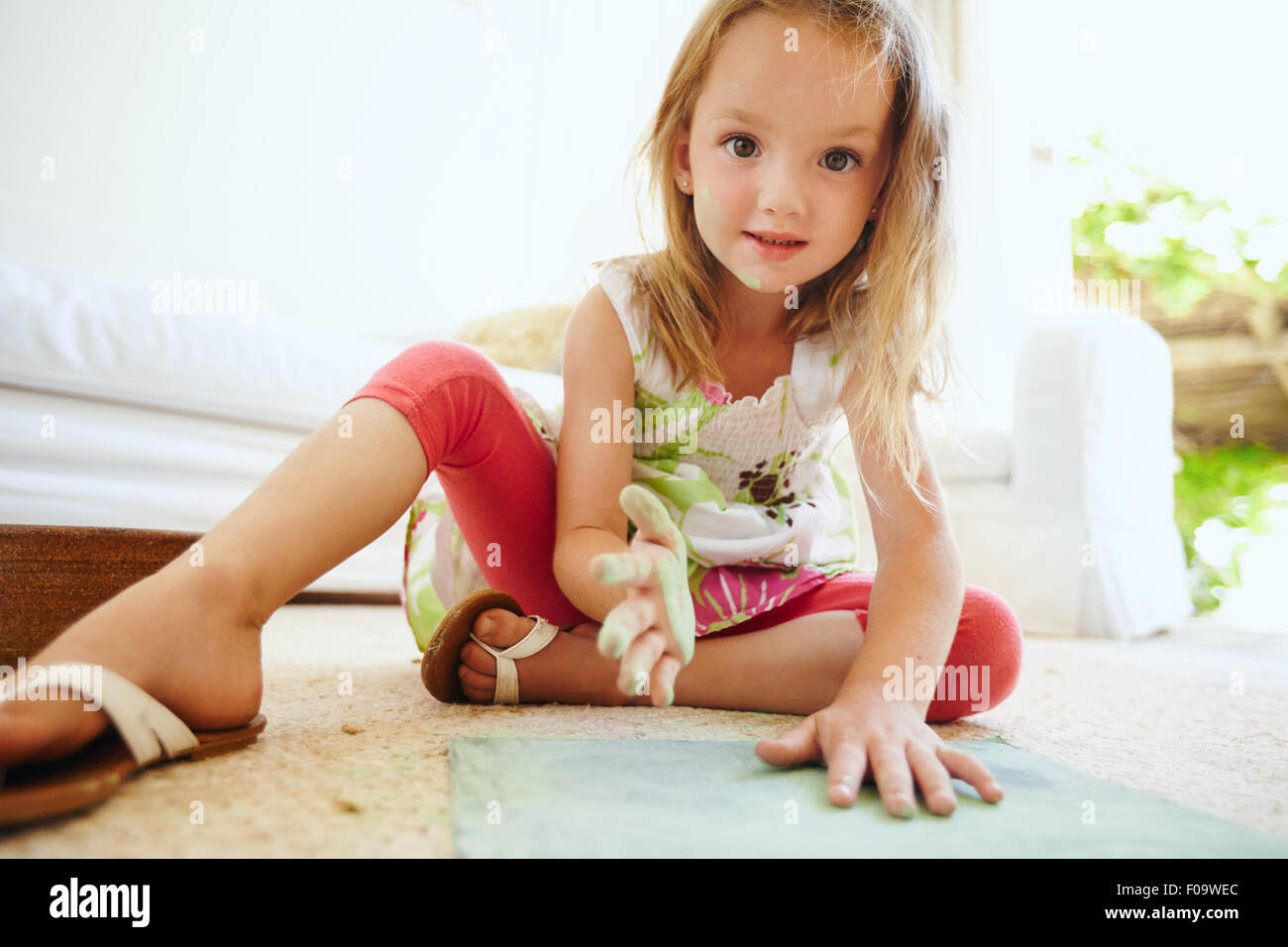 Portrait of beautiful little schoolgirl coloring a picture. Girl's hands painted with green chalk color looking - Stock Image