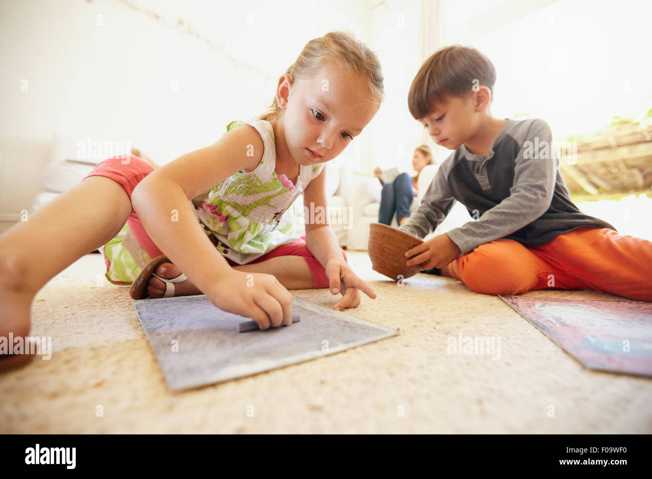 Little boy and girl coloring pictures with chalk colors while sitting on floor in living room at home. - Stock Image