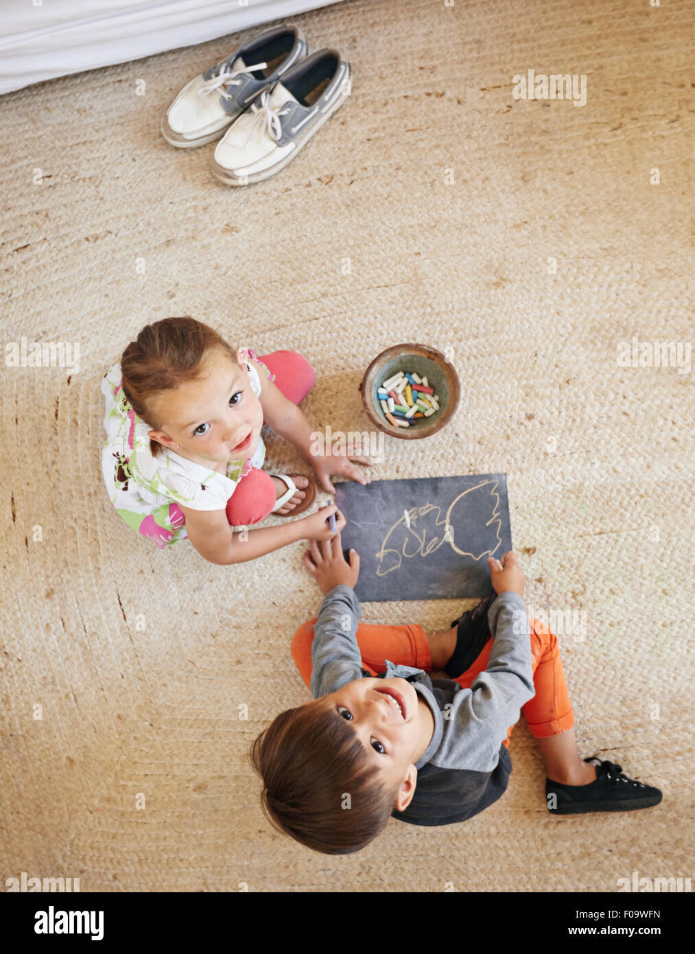 Top view of two little kids sitting on floor looking up at camera while drawing. - Stock Image