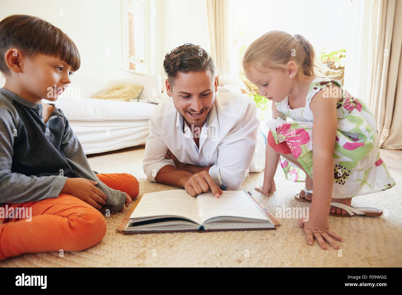 Family reading a book on the floor in the living room. Father reading stories to his son and daughter at home. Young - Stock Image