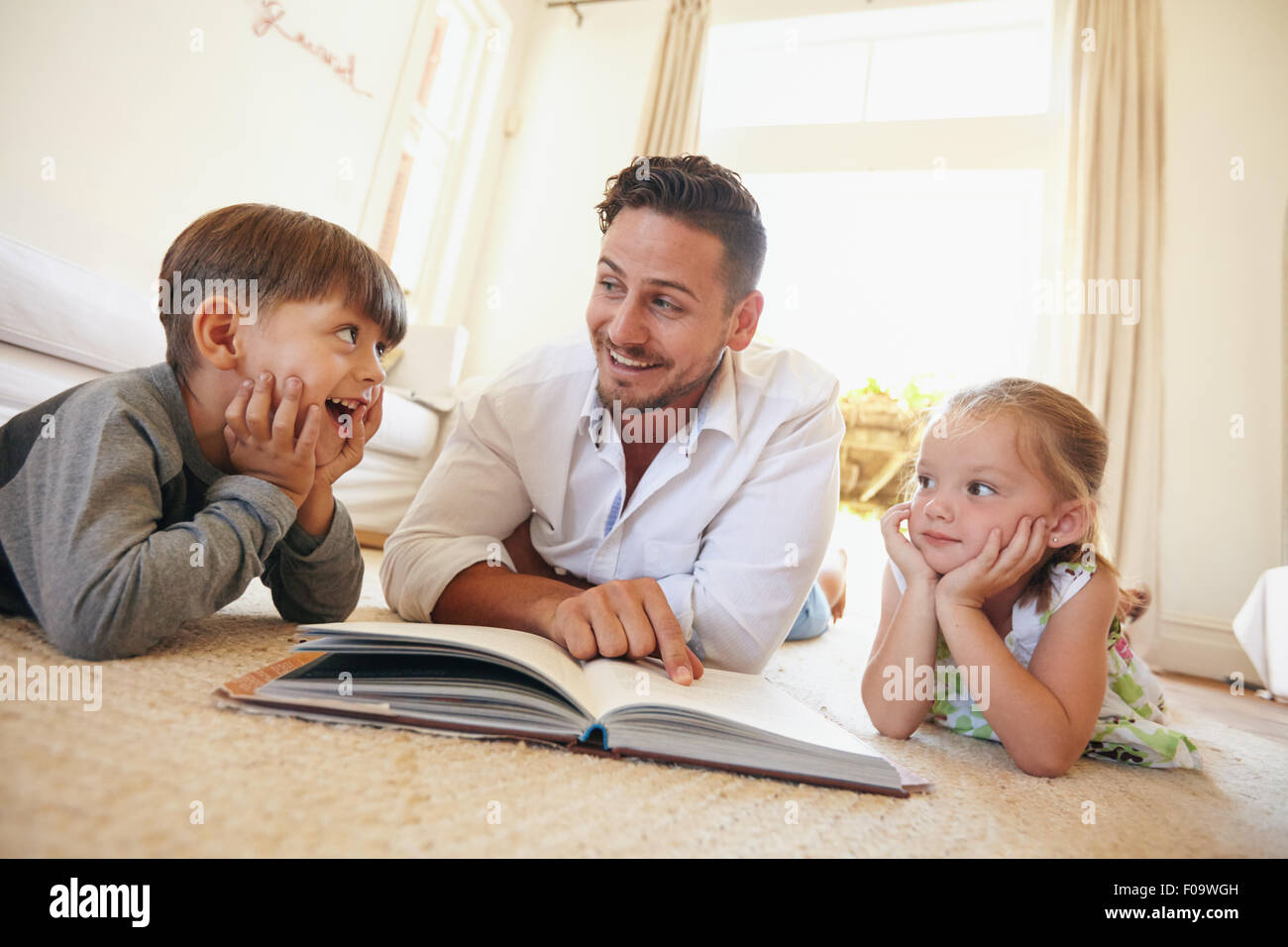 Shot of happy young family lying on the floor reading a book. Young man reading stories to his little son and daughter - Stock Image