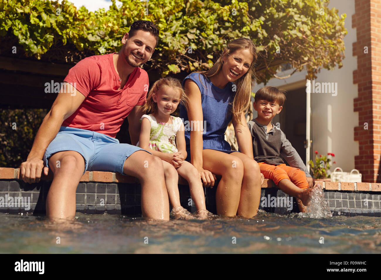 Family sitting with feet in swimming pool. Young family of four sitting on edge of their pool looking at camera - Stock Image