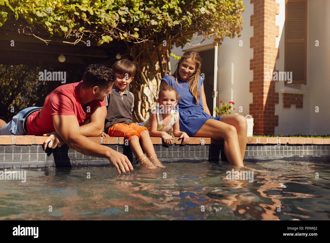 Portrait of young family with two children relaxing by their swimming pool having fun. Parents with kids sitting - Stock Image