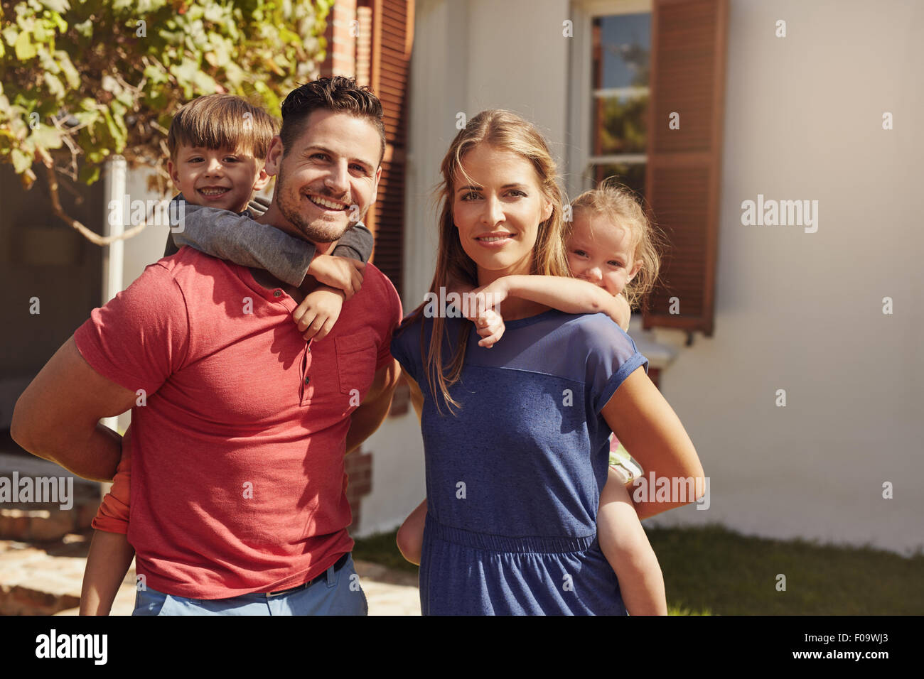 Outdoor shot of a happy couple carrying their children on their backs. Portrait of a mother and father giving their - Stock Image