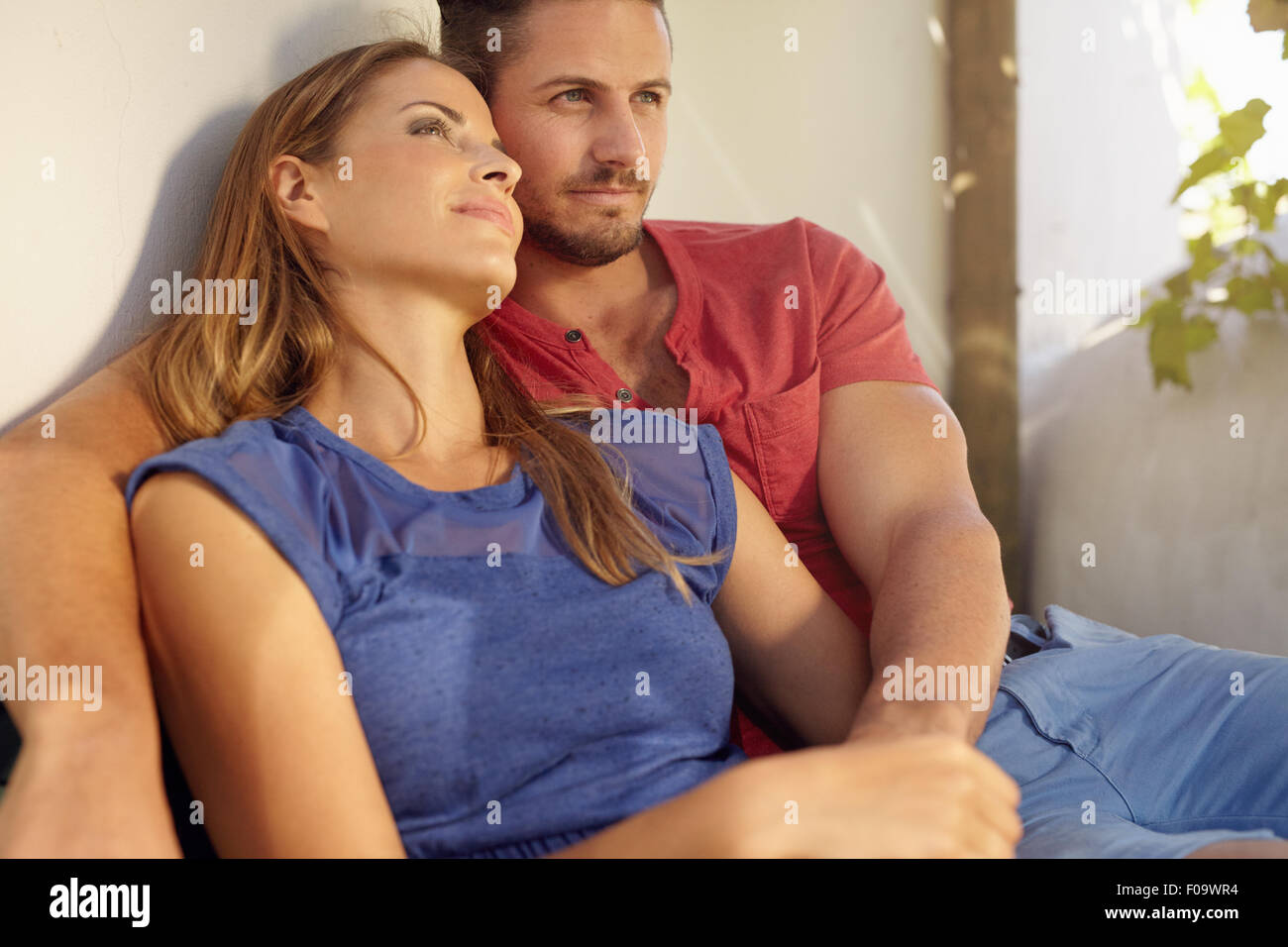 Outdoor shot of loving young man and woman sitting in their backyard. Love couple sitting relaxed together in patio. - Stock Image