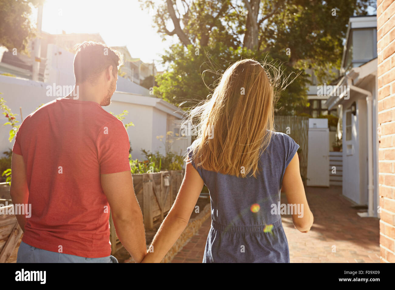 Rear view of young couple walking at their house together. Couple in backyard taking walk on a bright sunny day. - Stock Image