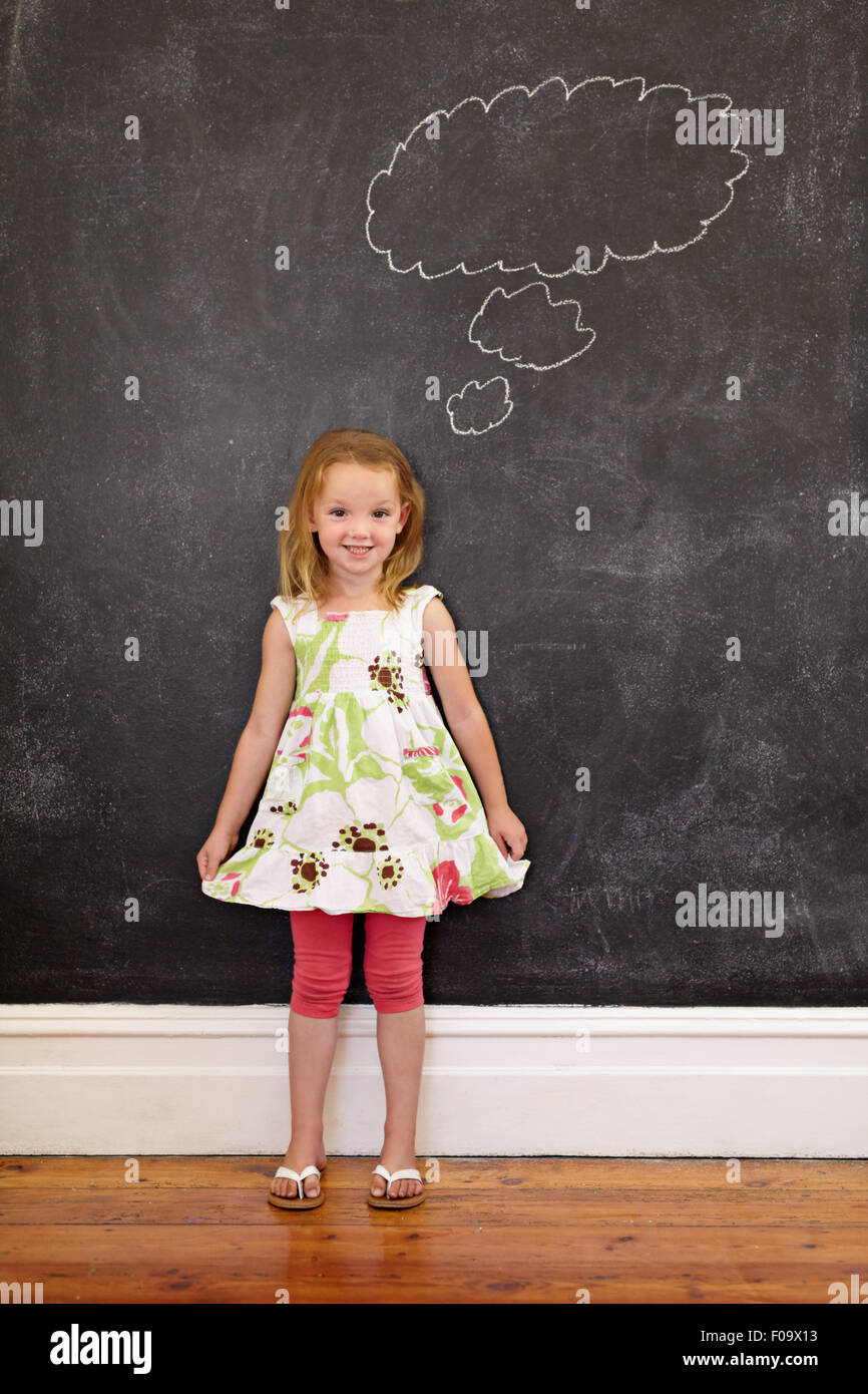 Full length shot of cute young girl in front of chalkboard with a thinking bubble, She is holding her dress looking - Stock Image