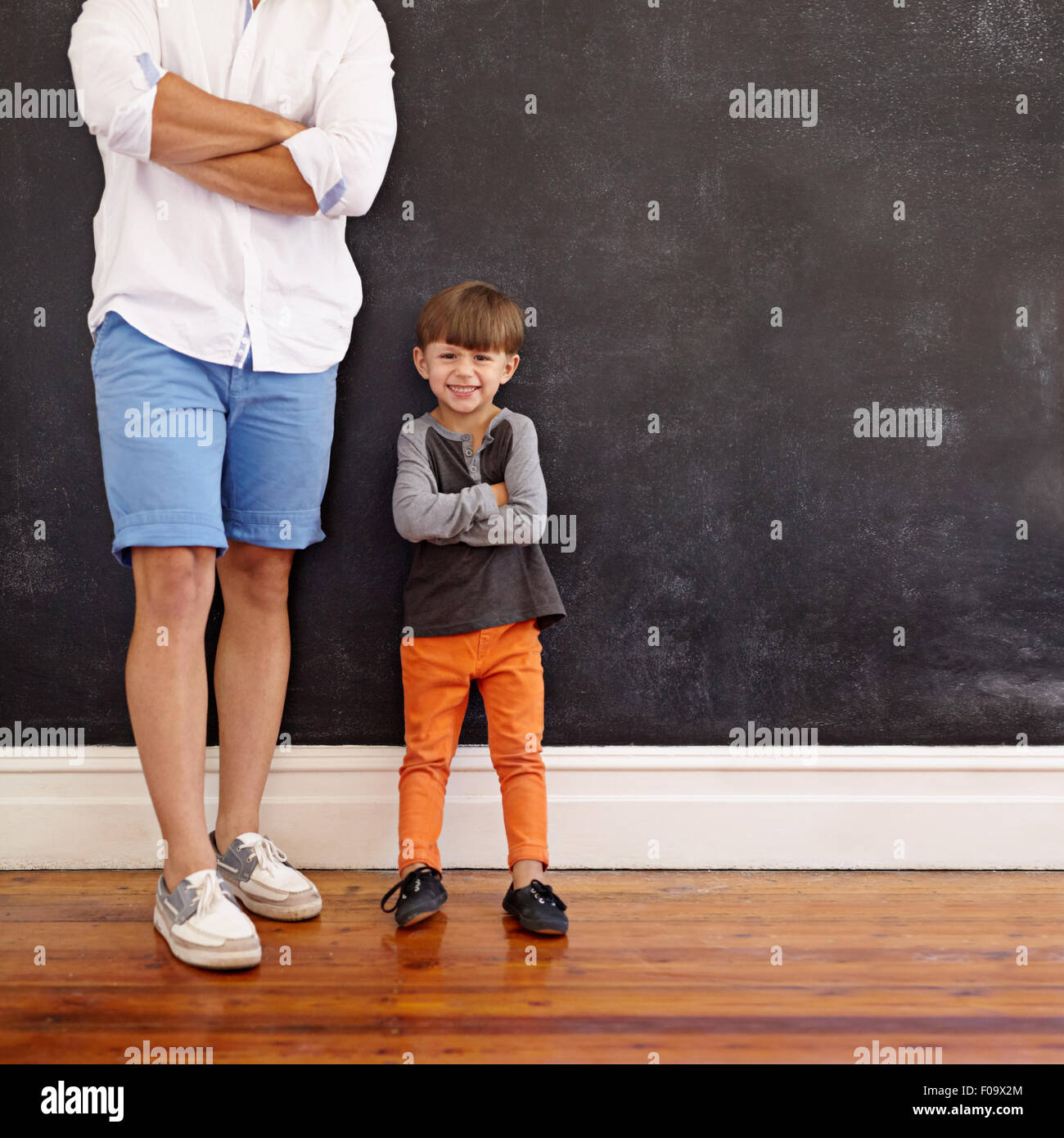 Indoor shot of little boy standing next to his father with hands folded and smiling.  Cropped shot of young man - Stock Image