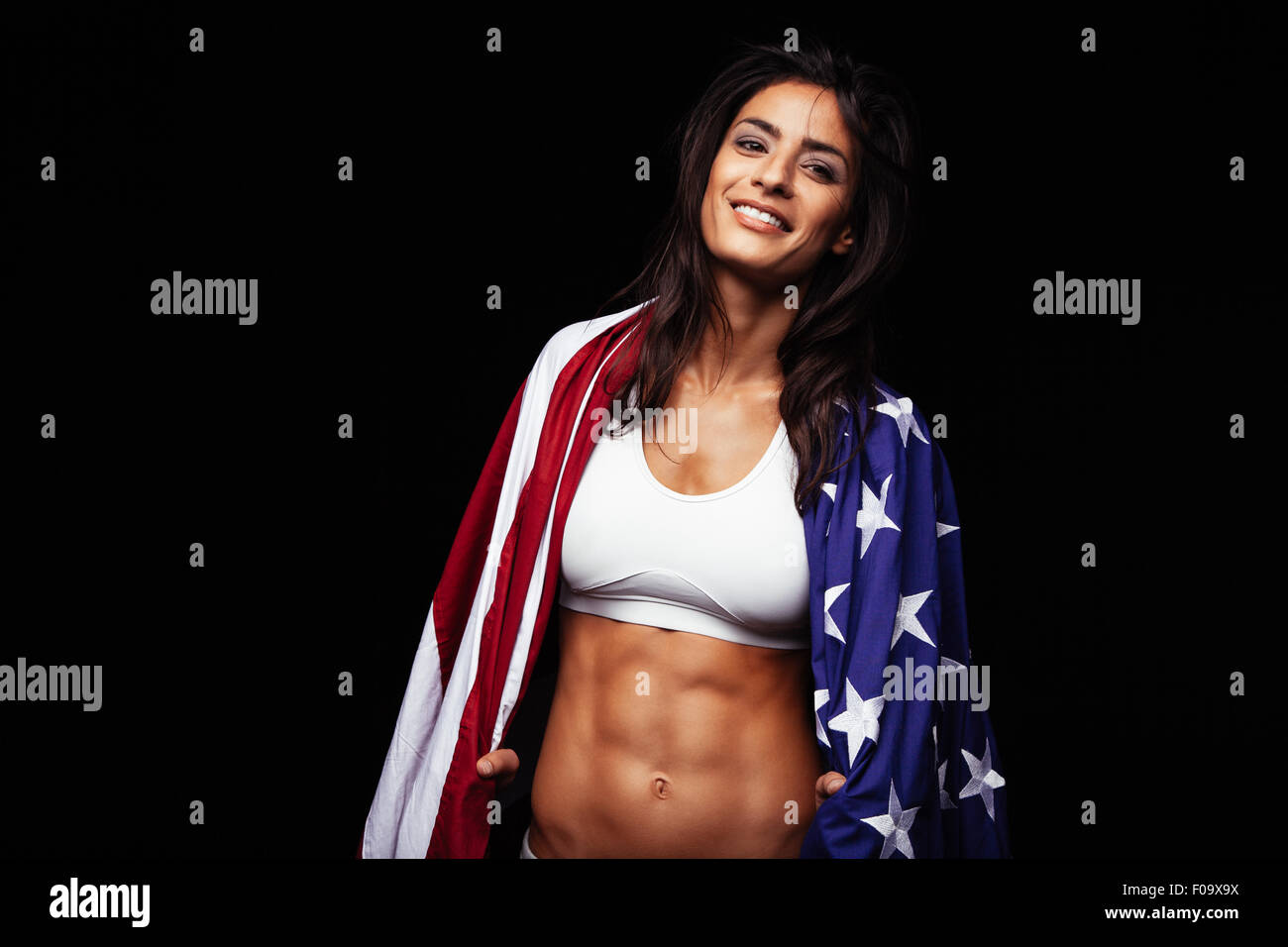 Portrait of happy young woman in sportswear holding American flag. Fit american female athlete wrapped in flag on - Stock Image