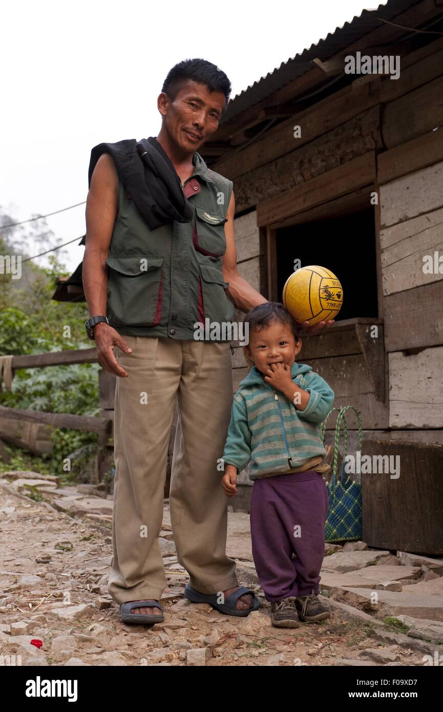 Man and boy standing besides a wooden shed in Mongar, Bhutan - Stock Image