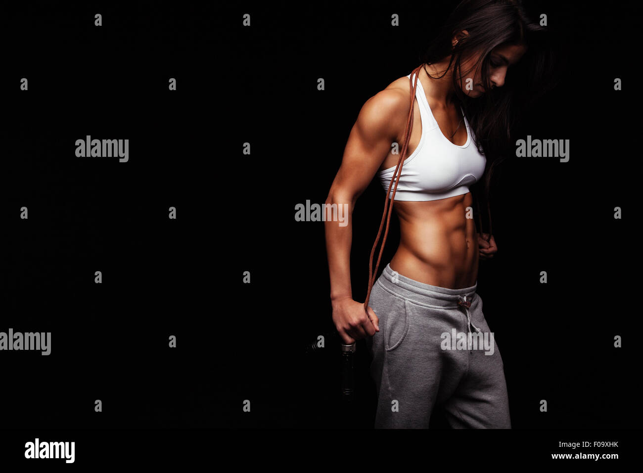 Image of female bodybuilder holding skipping rope looking down. Young fitness woman with muscular body posing on - Stock Image