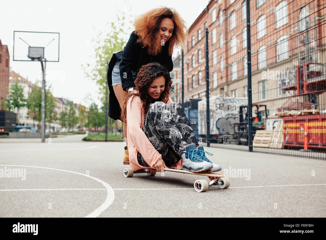 Playful photo of two women outdoors. Young woman sitting on longboard being pushed by her friend along the road. - Stock Image