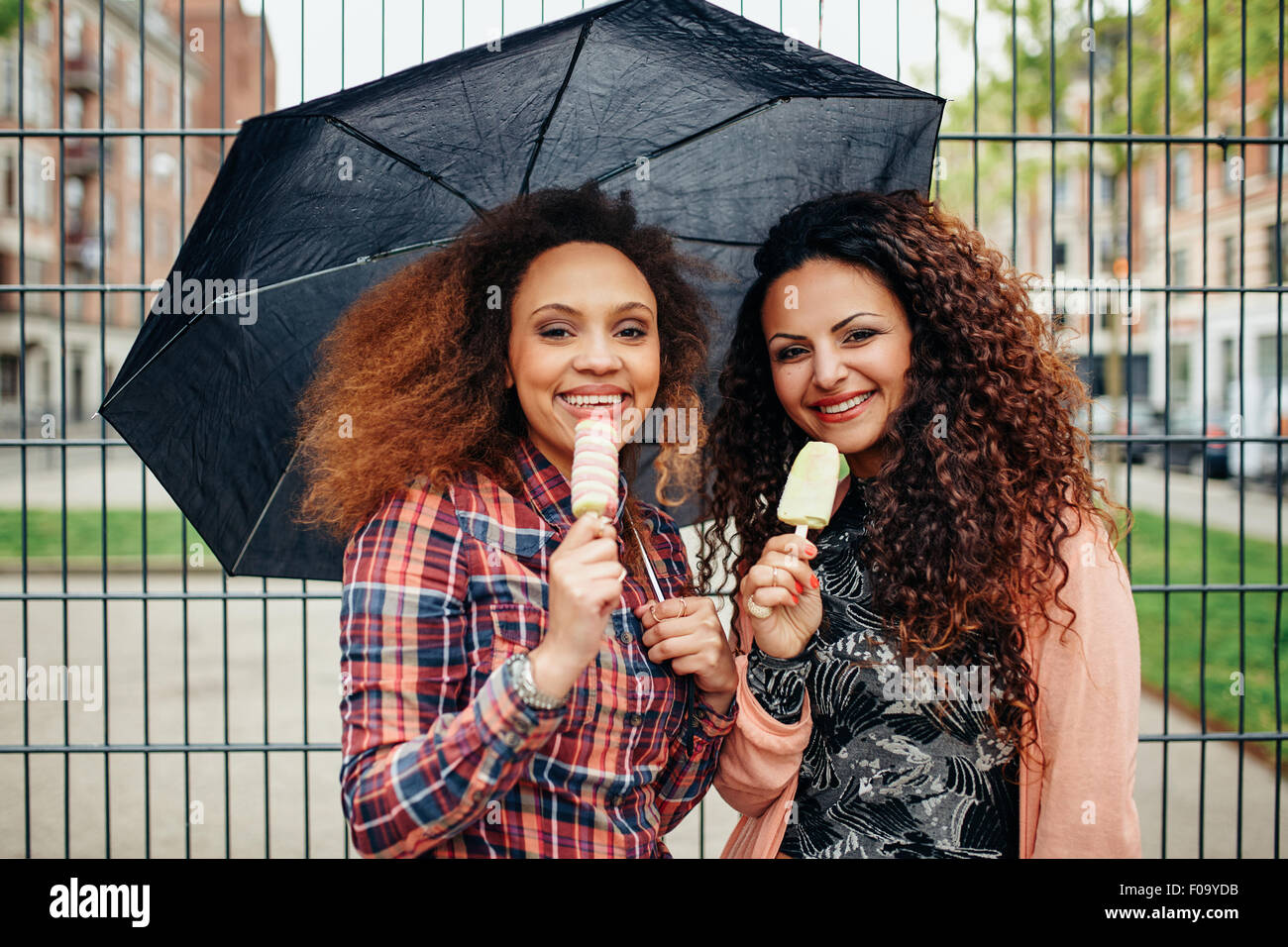 Portrait of two young women standing under umbrella eating an ice cream. Happy young female friends outdoor. - Stock Image