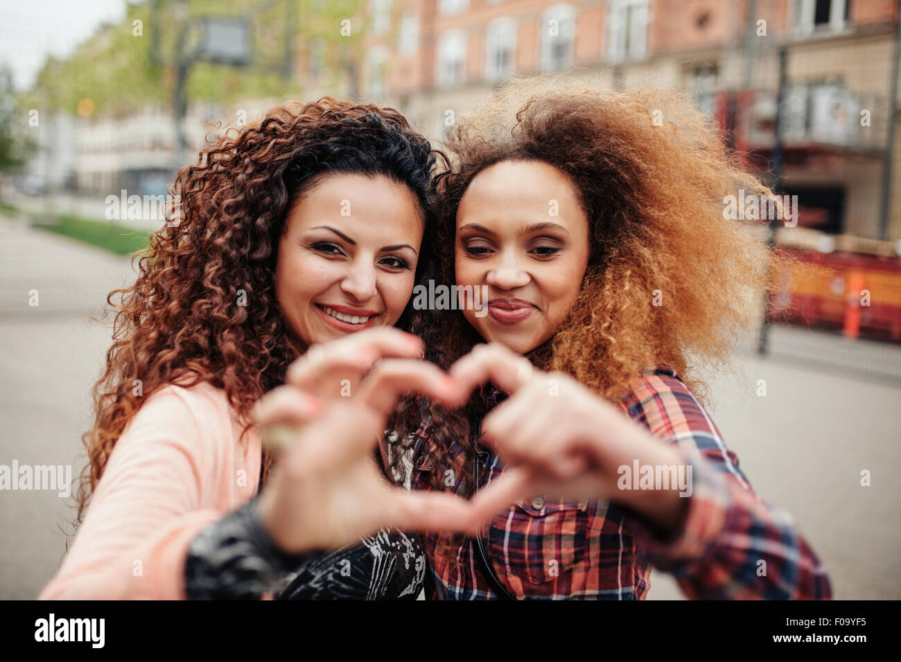 Beautiful young women making heart shape with fingers. Two women standing together outdoors on city street. - Stock Image