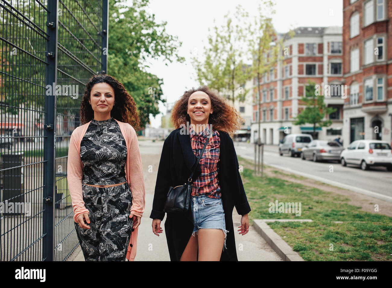 Outdoor shot of two girlfriends walking through town. Happy young women walking together along a city street. Stock Photo