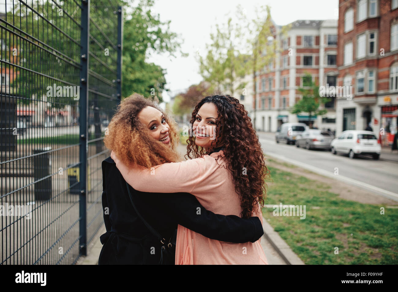 Outdoor shot of two girlfriends walking through town looking over shoulder smiling. Happy young women walking together - Stock Image