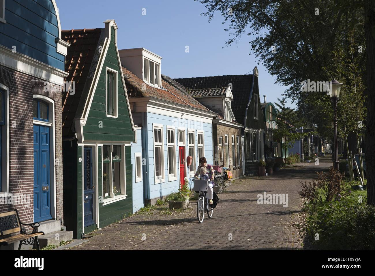 Woman cycling on road beside old captain's houses in Buiksloterdijk, Noord, Amsterdam Stock Photo